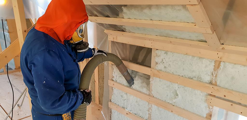installatör sprutar lösullsisolering i vägg